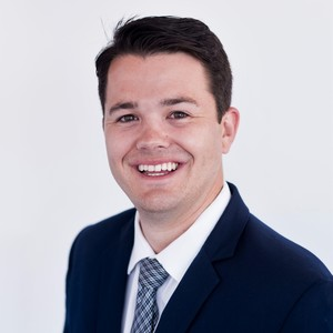 Headshot of a graduate student entrepreneur at the University of Texas at Austin -- he is smiling and wearing a suit and tie.
