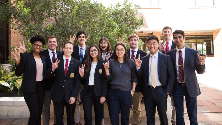 Group of diverse college students standing outside near trees posing for the camera after competing togehter in a entrepreneurship-centered pitch competition.