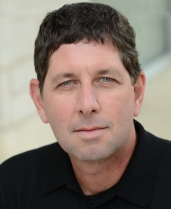 Middle-aged man with short-dark hair wearing a black-shirt looks seriously towards the camera